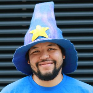 Kevin Kaland wearing a blended blue/purple wizard hat with a yellow star in the center near the brim.