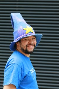 Kevin Kaland wearing a blended blue/purple wizard hat with a yellow star in the center near the brim. He is facing sideways.